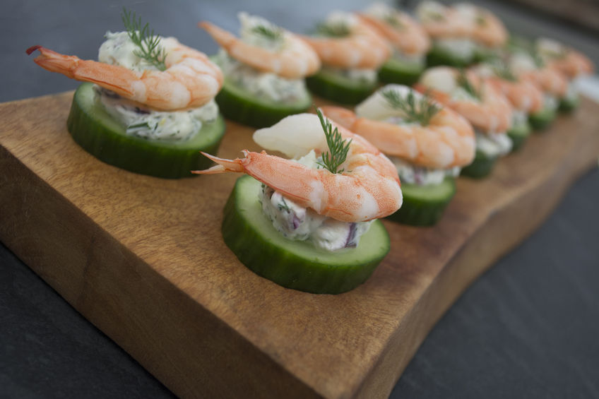 57218924 - shrimp cucumber and dill cream cheese round hor d'oeuvres on wooden serving tray