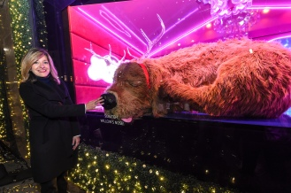 "Roya Sullivan, Macy's National Director of Window Presentation, scratches Willow's nose after Macy's Herald Square unveiled its iconic holiday windows celebrating the theme ""Believe in the Wonder,"" Thursday, Nov. 21, 2019, in New York. The six magical windows take spectators on a journey with Santa Girl as she embraces the spirit of the holidays. (Diane Bondareff/AP Images for Macy's)"